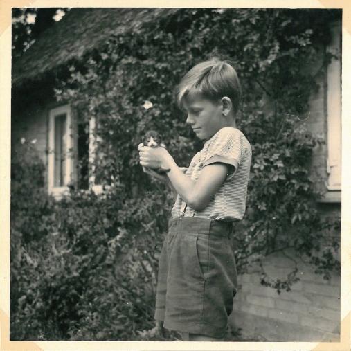 Torben med kattekilling ved det stråtækte hus på Møne 1957
